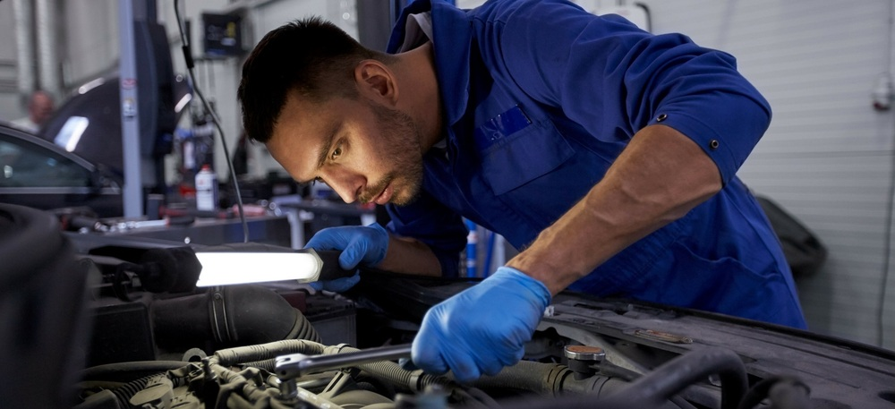 Automotive Service Technology- male mechanic working on a car under the hood